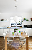 Dining table and modern chairs in front of long white sideboard