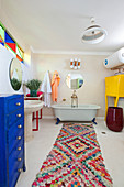 Free-standing bathtub and colourful accessories in large bathroom