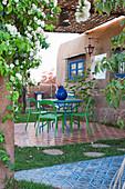 Modern garden furniture on terrace of patterned tiles outside house