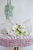 Bouquet of white tulips on stool with velvet cover
