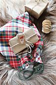 Kariertes Stoffsäckchen und verpackte Geschenke auf einem Fell