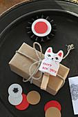 Papierkatze mit Neujahrsgruß an einem Geschenk