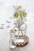 Weiße Christrosen in einer Vase mit Perlenkette als Winterdeko