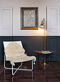 Sheepskin rug on easy chair, side table and standard lamp below drawing on wall