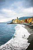 People walking along beach in Camogli, Liguria, Italy