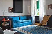 Blue sofa, side table and Indian armchair on blue patterned rug