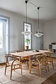 Designerstühle am Holztisch im Esszimmer mit hoher Decke