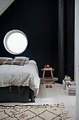 Bed below round window in black bedroom wall