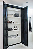 Fitted cupboard with black doors in white bathroom