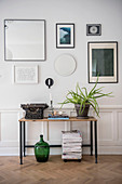 Console table against panelled wall with gallery of pictures