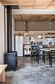 Wood-burning stove in rustic kitchen-dining room with concrete floor
