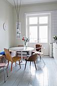 Verschiedene alte Stühle um runden Tisch in der Wohnküche im Altbau
