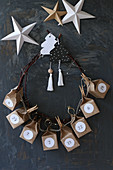 Handmade Advent calendar with numbered boxes made from brown paper threaded onto wreath