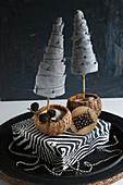 Zwei Mini-Tannenbäumchen aus Stoff auf Kiste mit Zebramotiv vor schwarzem Hintergrund