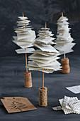 Mini-Tannenbäumchen aus Buchseiten auf Korken gespiesst vor schwarzem Hintergrund