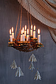 Suspended Advent wreath made from branches with lit candles and fir-tree pendants made from book pages