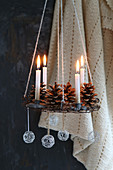 Suspended Advent wreath made from wire decorated with pine cones, wire balls and golden candles