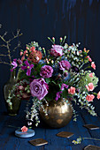 Vintage-style bouquet of roses, pinks, eucalyptus, clematis, proteas, Banksia, St. John's wort, sea holly and wild carrot