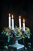 Advent wreath with hydrangea flowers and four candles in flower urn
