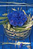 Gesteck mit Kornblumen in Kranz aus Weizenähren