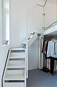 Clothes rail below staircase