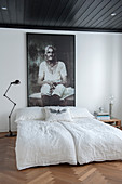Bild einer alten Frau überm Bett, Parkettboden und schwarze Decke