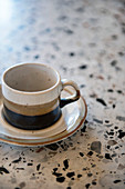 Three-coloured stoneware cup and saucer on terrazzo surface