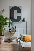 Large, framed letter C on wall above serving trolley against panelled wainscoting