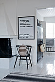 Raffia basket on chair below framed poster in Scandinavian house