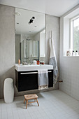 Large mirror above cubic sink unit in simple bathroom