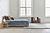 Bett und runder Nachttisch im minimalistischen Schlafzimmer