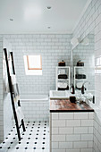 Ladder towel rack and bathtub in classic, attic bathroom with sloping wall