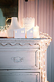 Wintry arrangement of lights in white on top of old chest of drawers