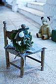 Vintage Kinderstuhl mit Weihnachtsgirlande und Teddybär im Hintergrund