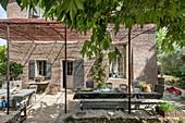 Überdachte Terrasse am französischen Landhaus im Sommer
