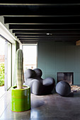 Cactus and designer armchair in living room with ceiling beams