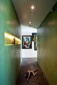 Skulptur am Boden einer ebenerdigen Dusche mit grünen Wänden
