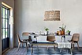 Cutlery and houseplants on rustic wooden table, chairs and bench
