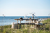 Crockery and lantern on wooden table next to sea
