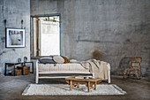 Rustic wooden bed, coffee table and rattan armchair