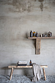 Bathroom utensils on wooden shelf above wooden bench
