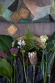 Still-life arrangement of flowers and leaves (hosta leaves, Swiss cheese plant leaf, sea lavender, allium, milkweed, fern, protea, Star-of-Bethlehem, sea holly, bird of paradise leaf)
