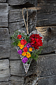 Wicker love-heart decorated with real geraniums and colourful paper flowers
