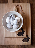 Easter eggs in bowl on wooden boards with Easter bunny motifs