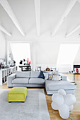 Pale grey corner sofa in open-plan interior with exposed, white ceiling beams