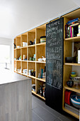 Chalkboard sliding door flanked by shelves of crockery in kitchen