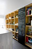 Chalkboard sliding door flanked by shelves of crockery in kitchen
