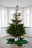 Decorated Christmas tree on rug made from green circles in room with bay window