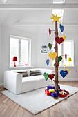 Baumstamm mit bunten Herzen als alternativer Weihnachtsbaum