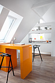 Orange, retro desk in open-plan attic apartment